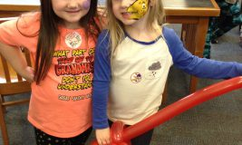 2 girls with facepainting and balloon at Take Your Child to the Library Day